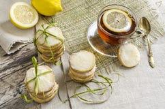 Selbst gemachte Zitronenzuckerplätzchen und Schale heißer Tee auf Leinentischdecke Lizenzfreie Stockfotos