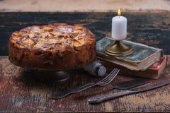 Selbst gemachter Apfelkuchen und Kerze und alte Bücher Stockfotografie