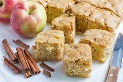 Selbst gemachter blondie (blonder) Schokoladenkuchen-Apfelkuchen, quadratische Scheiben auf Pergament Lizenzfreie Stockfotos