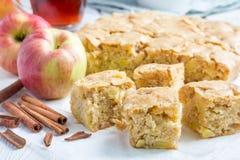 Selbst gemachter blondie (blonder) Schokoladenkuchen-Apfelkuchen, quadratische Scheiben auf Pergament Stockfoto