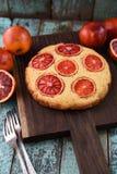Selbst gemachter Blutorangekuchen mit rohen Orangen auf dunklem Eichenbrett an Stockbilder