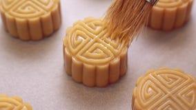 Selbst gemachter cantonese Mondkuchen bevor dem Backen - Frau, die Ei auf Gebäck mit Bürste auf Backblech für traditionelles Fest stock video footage