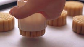 Selbst gemachter cantonese Mondkuchen bevor dem Backen - Frau, die festliches Gebäck mit der Formung der Form auf Backblech für t stock footage