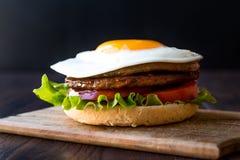 Selbst gemachter doppelter Hamburger mit Ei, Kopfsalat und Tomaten stockfotografie