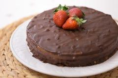 Selbst gemachter dunkler Schokoladenkuchen mit Kakao und frischen organischen Erdbeeren auf die Oberseite diente auf einem weißen Lizenzfreies Stockfoto