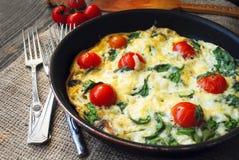 Selbst gemachter Frittata mit Tomaten und Kräutern Stockbild