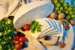 selbst gemachter georgischer Imeretian-Käse auf einem hölzernen Brett, Kirschtomaten, Walnüsse, Trauben lizenzfreie stockfotografie