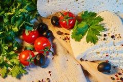 selbst gemachter georgischer Imeretian-Käse auf einem hölzernen Brett, Kirschtomaten, Walnüsse, Trauben, Gewürze stockfotos