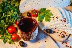 selbst gemachter georgischer Imeretian-Käse auf einem hölzernen Brett, Kirschtomaten, Walnüsse, Trauben, Gewürze stockfotografie