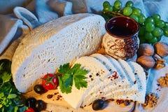 selbst gemachter georgischer Imeretian-Käse auf einem hölzernen Brett, Kirschtomaten, Walnüsse, Trauben, Gewürze lizenzfreie stockfotografie