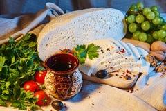 selbst gemachter georgischer Imeretian-Käse auf einem hölzernen Brett, Kirschtomaten, Walnüsse, Trauben, Gewürze lizenzfreies stockfoto