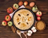 Selbst gemachter geschmackvoller Apfelkuchen mit Apfel-und Gewürz-hölzernen Hintergrund-Draufsicht-rohen Äpfel Cinnamone-Stöcken Stockfotos