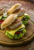 Selbst gemachter geschmackvoller Hamburger oder Cheeseburger Stockfotos