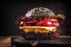 Selbst gemachter Hamburger Schwarze Kichererbse des Veggie mit einem Kotelett, Tomate, Käse, dunklem Kopfsalat und purpurroter Zw stockbild