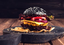 Selbst gemachter Hamburger Schwarze Kichererbse des Veggie mit einem Kotelett, Tomate, Käse, dunklem Kopfsalat und purpurroter Zw Lizenzfreie Stockfotografie