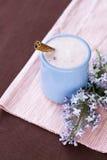 Selbst gemachter Jogurt in einer keramischen Schüssel auf einer rosa Tischdecke, Zimtstange und einem Zweig der Flieder Stockbild