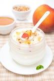 Selbst gemachter Jogurt mit Honig, Pfirsiche, Nüsse in einem Löffel Lizenzfreie Stockbilder