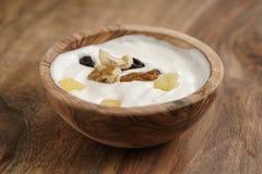 Selbst gemachter Jogurt mit muesli in der hölzernen Schüssel auf Holztisch Lizenzfreie Stockfotos