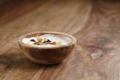 Selbst gemachter Jogurt mit muesli in der hölzernen Schüssel auf Holztisch Stockfotos