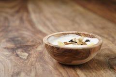 Selbst gemachter Jogurt mit muesli in der hölzernen Schüssel auf Holztisch Stockfotografie