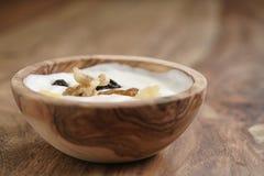 Selbst gemachter Jogurt mit muesli in der hölzernen Schüssel auf Holztisch Lizenzfreie Stockbilder
