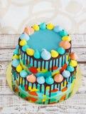 selbst gemachter Kind-2-tiered ` s Kuchen verziert mit buntem Fleck mit Meringe auf weißem Hintergrund stockfotos