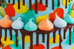 selbst gemachter Kind-2-tiered ` s Kuchen verziert mit buntem Fleck mit Meringe auf weißem Hintergrund stockbilder