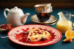 Selbst gemachter Käsekuchen mit Zitrone Klumpen- und gojibeeren auf Rot flechten Stockfoto