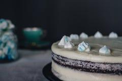 Selbst gemachter Kuchen der Schokolade mit Sahne verziert mit französischen Meringen und einem Becher auf einem dunklen Hintergru lizenzfreie stockfotos
