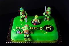 Selbst gemachter Kuchen mit ` Mastixdekor und -aufschrift ` Matvei 6 für Kind-` s Geburtstag auf einem dunklen Hintergrund Stockbilder