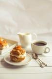 Selbst gemachter neuer Windbeutel mit Schlagsahne und Aprikosen, Tasse Kaffee und Milchkrug Lizenzfreies Stockfoto