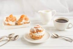 Selbst gemachter neuer Windbeutel mit Schlagsahne und Aprikosen, Tasse Kaffee und Milchkrug tonen Stockbilder
