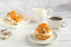Selbst gemachter neuer Windbeutel mit Schlagsahne und Aprikosen, Tasse Kaffee und Milchkrug tonen Stockbild