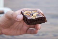 Selbst gemachter Schokoladenschokoladenkuchen mit Acajounuss in der linken Hand Lizenzfreie Stockfotos