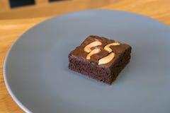 Selbst gemachter Schokoladenschokoladenkuchen mit Acajounuss im Teller Stockbilder