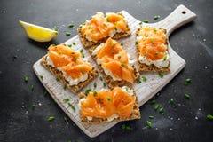 Selbst gemachter Toast des knusprigen Brotes mit geräuchertem Lachs und weiche chees, Schnittlauche auf weißem Brett Lizenzfreie Stockfotografie