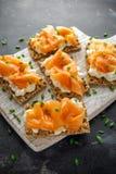 Selbst gemachter Toast des knusprigen Brotes mit geräuchertem Lachs und weiche chees, Schnittlauche auf weißem Brett Lizenzfreies Stockbild