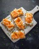 Selbst gemachter Toast des knusprigen Brotes mit geräuchertem Lachs und weiche chees, Schnittlauche auf weißem Brett Stockfoto