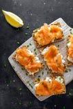 Selbst gemachter Toast des knusprigen Brotes mit geräuchertem Lachs und weiche chees, Schnittlauche auf weißem Brett Lizenzfreie Stockfotos