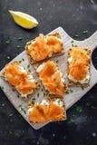 Selbst gemachter Toast des knusprigen Brotes mit geräuchertem Lachs und weiche chees, Schnittlauche auf weißem Brett Stockbilder