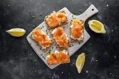 Selbst gemachter Toast des knusprigen Brotes mit geräuchertem Lachs und weiche chees, Schnittlauche auf weißem Brett Lizenzfreies Stockfoto