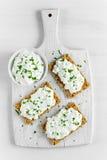 Selbst gemachter Toast des knusprigen Brotes mit Hüttenkäse und Petersilie auf weißem Hintergrund des hölzernen Brettes Stockfoto