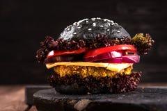 Selbst gemachter Veggieschwarz-Kichererbsenburger mit einem Kotelett, Tomate, Käse, dunklem Salat und purpurroter Zwiebel auf rus Lizenzfreies Stockbild