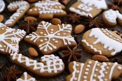 Selbst gemachter Weihnachtslebkuchen auf einem hölzernen Hintergrund mit Sternanis und -mandel Stockbilder