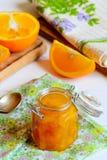Selbst gemachter Zitrusfruchtstau Süßorangestau in einem Glasgefäß, Textilserviette, neue orange Scheiben auf einer Tabelle Gesun Stockbild