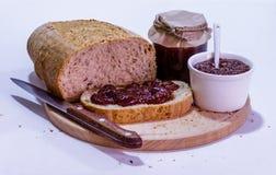 Selbst gemachtes Brot mit Erdbeermarmelade auf hölzerner Platte Stockbild