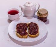 Selbst gemachtes Brot mit Erdbeermarmelade und Tasse Tee Lizenzfreies Stockbild