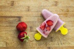 Selbst gemachtes Erdbeereis am stiel mit Beeren auf hölzernem Hintergrund Flache Lage Beschneidungspfad eingeschlossen Lizenzfreie Stockfotos