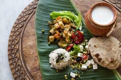Selbst gemachtes Ernährungsgemüseragout, Reis, Salat, Jogurt, Chapati auf Bananenblatt Lizenzfreies Stockfoto