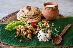 Selbst gemachtes Ernährungsgemüseragout, Reis, Salat, Jogurt, Chapati auf einem Bananenblatt Stockbilder